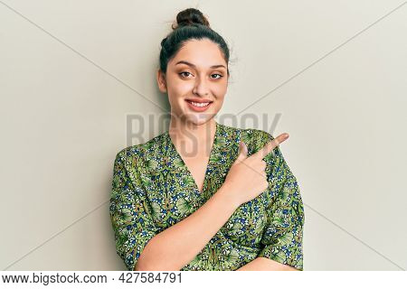 Beautiful middle eastern woman wearing casual clothes smiling cheerful pointing with hand and finger up to the side