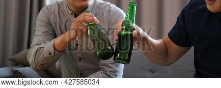 Happy Two Men Sitting On Couch And Clinking Bottles Of Beer Together.