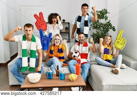 Group of friends supporting football team watching tv al home sitting on the sofa annoyed and frustrated shouting with anger, yelling crazy with anger and hand raised