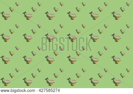 Repeated Children Toy Figurine Of Goose On A Colored Background. Alternating Plastic Poultry Against