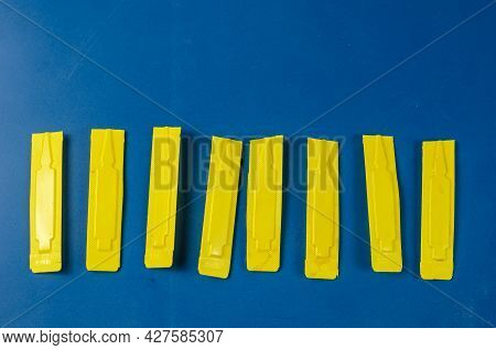 Dog Flea And Tick Drops Against Blue. Yellow Plastic Container With Veterinary Antiparasitic Drug Fo