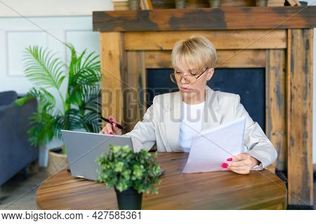 Woman In Glasses Works With Documents In Front Of A Laptop Monitor. She Checks The Tax Records Befor