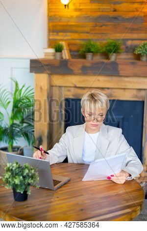 Woman In Front Of A Laptop Monitor. She Is Concentrated And Works With Documents And Papers At Home