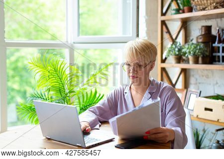 Woman In Pajama Works With Documents In Front Of A Laptop Monitor In Home Interior. She Checks The T