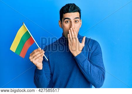 Handsome hispanic man holding lithuania flag covering mouth with hand, shocked and afraid for mistake. surprised expression