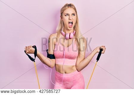 Young beautiful caucasian woman training arm resistance with elastic arm bands angry and mad screaming frustrated and furious, shouting with anger looking up.