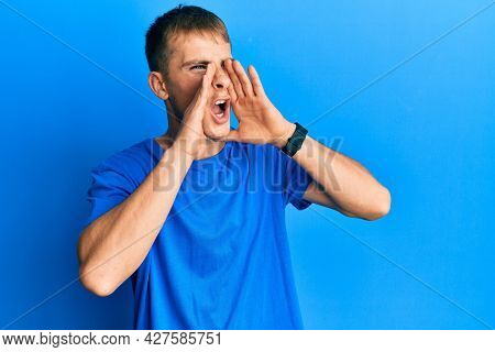 Young caucasian man wearing casual blue t shirt shouting angry out loud with hands over mouth