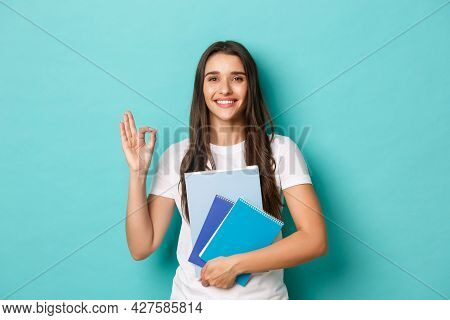 Portrait Of Young Female Student In White T-shirt, Holding Notebooks And Showing Okay Sign, Smiling