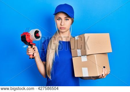 Young caucasian woman holding packages and packing tape depressed and worry for distress, crying angry and afraid. sad expression.