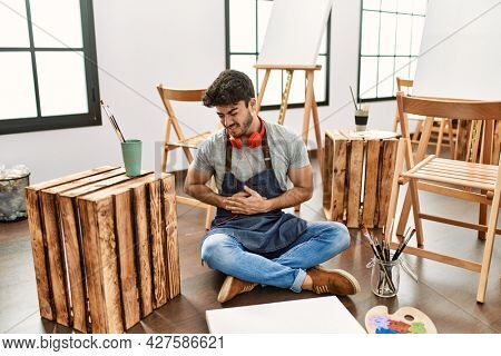 Young hispanic man sitting at art studio with hand on stomach because nausea, painful disease feeling unwell. ache concept.