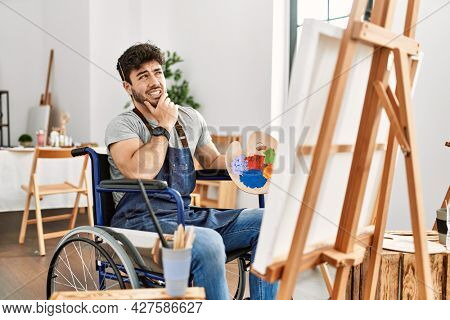 Young hispanic man sitting on wheelchair painting at art studio thinking worried about a question, concerned and nervous with hand on chin