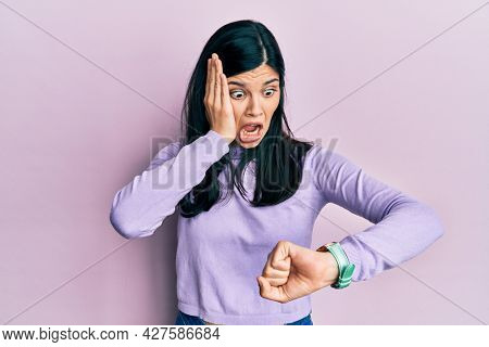 Young hispanic woman wearing casual clothes looking at the watch time worried, afraid of getting late
