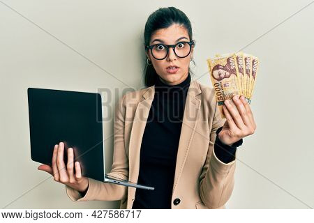 Young hispanic woman wearing business style holding laptop and hungarian forint in shock face, looking skeptical and sarcastic, surprised with open mouth