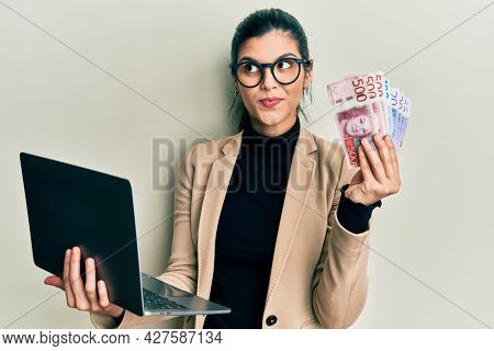 Young hispanic woman wearing business style holding laptop and swedish krone smiling looking to the side and staring away thinking.