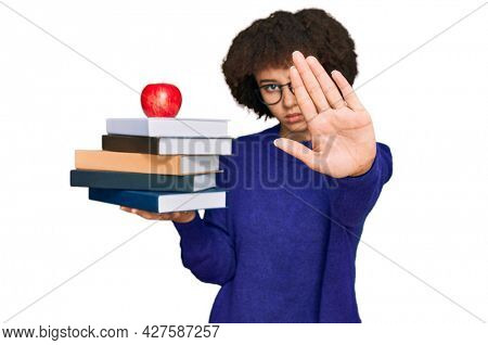 Young hispanic girl wearing glasses holding books and red apple with open hand doing stop sign with serious and confident expression, defense gesture