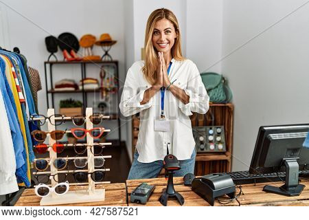 Blonde beautiful young woman working as manager at retail boutique praying with hands together asking for forgiveness smiling confident.