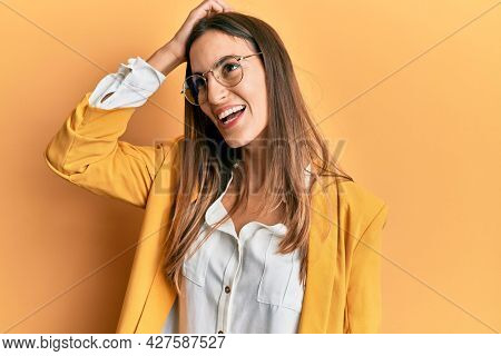 Young beautiful woman wearing business style and glasses smiling confident touching hair with hand up gesture, posing attractive and fashionable