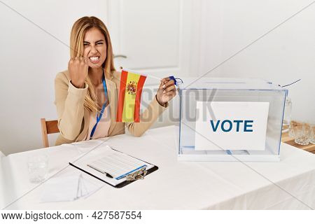Blonde beautiful young woman at political campaign election holding spain flag annoyed and frustrated shouting with anger, yelling crazy with anger and hand raised