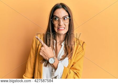 Young beautiful woman wearing business style and glasses pointing aside worried and nervous with forefinger, concerned and surprised expression
