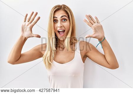 Blonde beautiful young woman standing over white isolated background showing and pointing up with fingers number ten while smiling confident and happy.