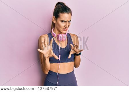 Young beautiful woman wearing gym clothes and using headphones disgusted expression, displeased and fearful doing disgust face because aversion reaction. with hands raised