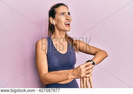 Young beautiful woman wearing gym clothes, using earphones and smart watch angry and mad screaming frustrated and furious, shouting with anger looking up.