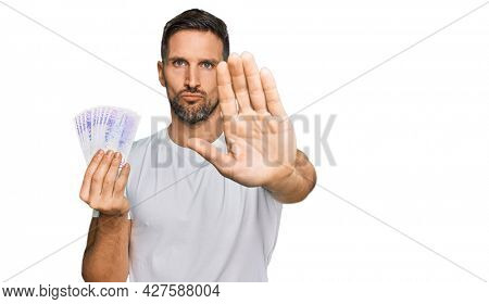 Handsome man with beard holding 20 swedish krona banknotes with open hand doing stop sign with serious and confident expression, defense gesture