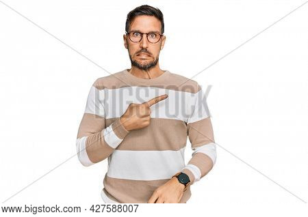 Handsome man with beard wearing casual clothes and glasses pointing aside worried and nervous with forefinger, concerned and surprised expression