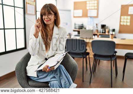Hispanic business woman working at the office gesturing finger crossed smiling with hope and eyes closed. luck and superstitious concept.