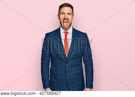 Handsome man with beard wearing business suit and tie sticking tongue out happy with funny expression. emotion concept.