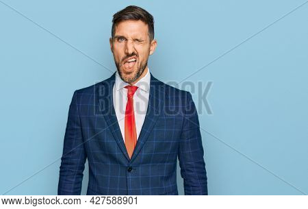 Handsome man with beard wearing business suit and tie winking looking at the camera with sexy expression, cheerful and happy face.