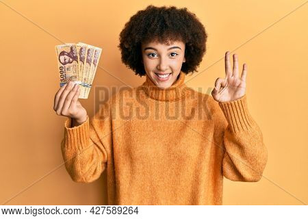 Young hispanic girl holding 5000 hungarian forint banknotes doing ok sign with fingers, smiling friendly gesturing excellent symbol