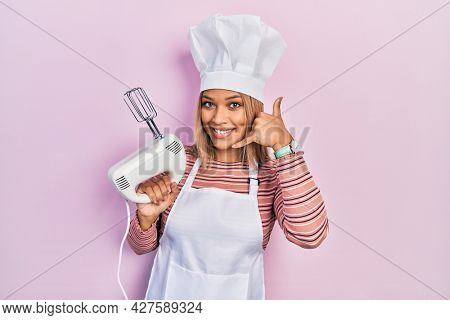 Beautiful hispanic woman holding pastry blender electric mixer smiling doing phone gesture with hand and fingers like talking on the telephone. communicating concepts.