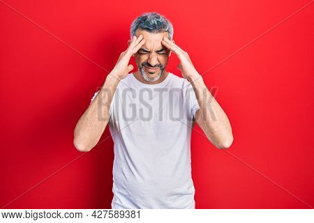 Handsome middle age man with grey hair wearing casual white t shirt suffering from headache desperate and stressed because pain and migraine. hands on head.