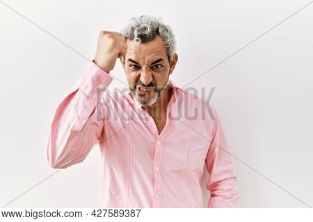 Middle age hispanic man standing over isolated background angry and mad raising fist frustrated and furious while shouting with anger. rage and aggressive concept.