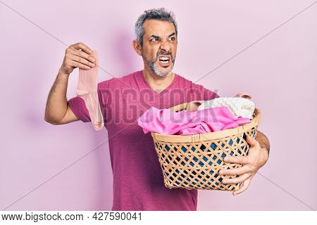 Handsome middle age man with grey hair holding laundry basket and dirty sock angry and mad screaming frustrated and furious, shouting with anger. rage and aggressive concept.