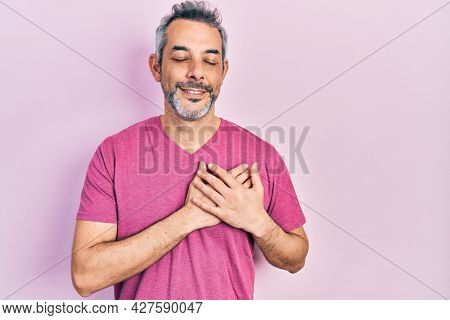 Handsome middle age man with grey hair wearing casual pink t shirt smiling with hands on chest, eyes closed with grateful gesture on face. health concept.