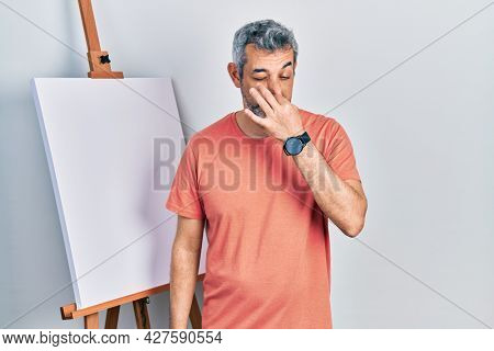 Handsome middle age man with grey hair standing by painter easel stand smelling something stinky and disgusting, intolerable smell, holding breath with fingers on nose. bad smell