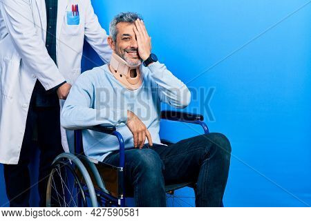 Handsome middle age man with grey hair on wheelchair wearing cervical collar covering one eye with hand, confident smile on face and surprise emotion.