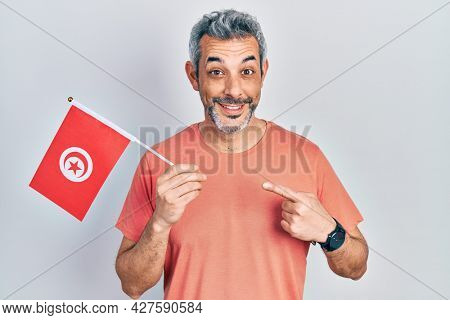 Handsome middle age man with grey hair holding tunisia flag smiling happy pointing with hand and finger