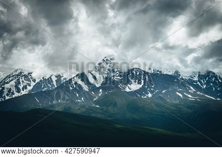 Dramatic Mountains Landscape With Big Snowy Mountain Ridge In Low Clouds Above Sunlit Forest In Over