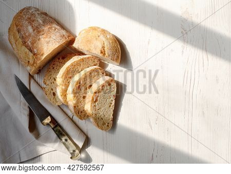 Sliced Organic Bread Ciabatta With Vintage Linen Napkin And Knife On White Wooden Background. Top Vi