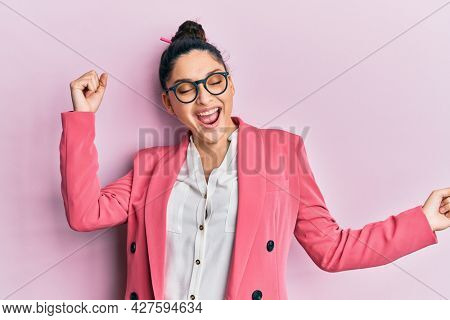 Beautiful middle eastern woman wearing business jacket and glasses dancing happy and cheerful, smiling moving casual and confident listening to music