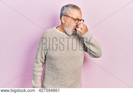 Handsome senior man with beard wearing casual sweater and glasses smelling something stinky and disgusting, intolerable smell, holding breath with fingers on nose. bad smell
