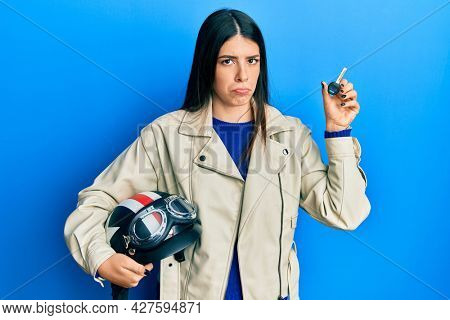 Young hispanic woman holding motorcycle helmet and key depressed and worry for distress, crying angry and afraid. sad expression.