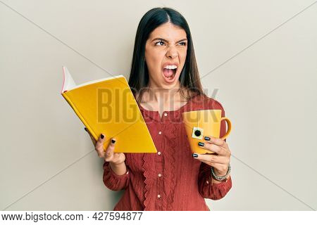Young hispanic woman reading book drinking cup of tea angry and mad screaming frustrated and furious, shouting with anger. rage and aggressive concept.