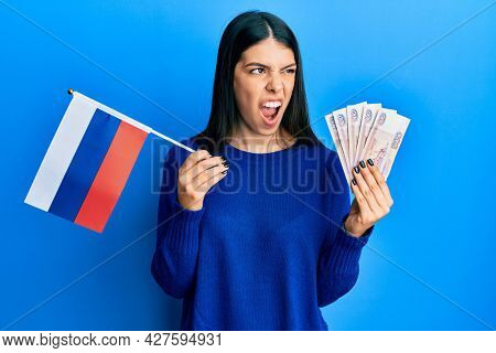 Young hispanic woman holding russia flag and rubles banknotes angry and mad screaming frustrated and furious, shouting with anger. rage and aggressive concept.