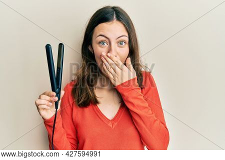 Young brunette woman holding hair straightener covering mouth with hand, shocked and afraid for mistake. surprised expression