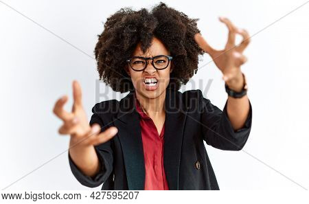 African american woman with afro hair wearing business jacket and glasses shouting frustrated with rage, hands trying to strangle, yelling mad