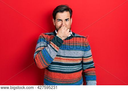 Handsome caucasian man with beard wearing elegant wool winter sweater smelling something stinky and disgusting, intolerable smell, holding breath with fingers on nose. bad smell